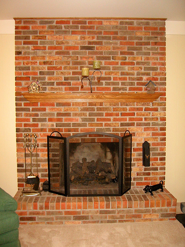 brick and oak mantel look could use some updating - a perfect fireplace